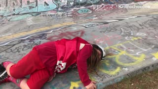 Girl in red outfit falls off skateboard
