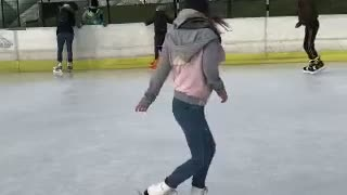 Girl in pink spins on ice spins and falls slow motion - Video