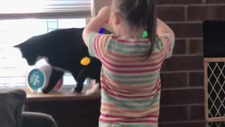 Little girl decorates cat with Christmas lights - Video