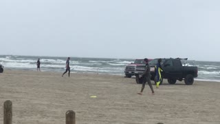 Guy in wetsuit misses yellow frisbee on beach - Video