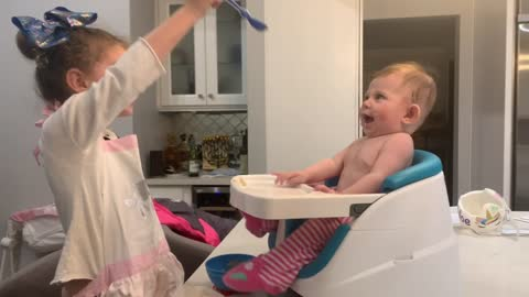 Baby boy ecstatic while being fed by big sister