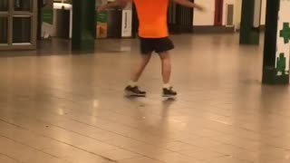 Guy orange shirt bald spinning in subway train station - Video