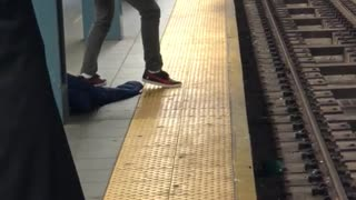 Man with long curly black hair sings on subway platform