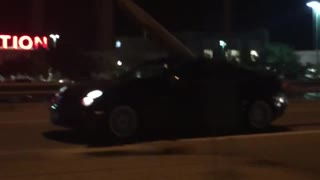 Black car with surfboard coming out of moonroof - Video