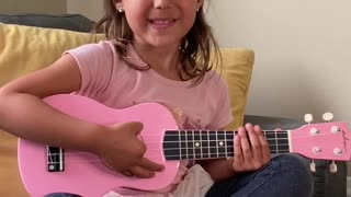 Five year old giving ukulele lesson
