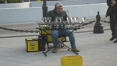 Street performer amazingly plays music on water glasses