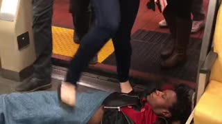 Guy laying on subway floor people walking over him - Video