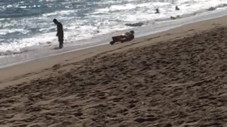 Man rolls down sand towards beach