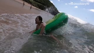 Woman in avocado floaty is flipped by wave  - Video