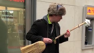 Street performer turns broom into electric guitar