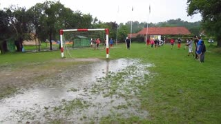 Man with hat jumps into muddy puddle in soccer field  - Video