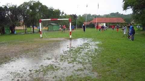 Man with hat jumps into muddy puddle in soccer field