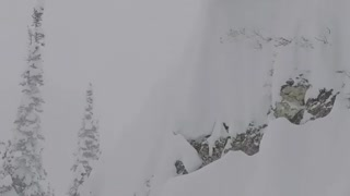 WHERE DID HE GO? Dude skis off high ledge into deep snow.