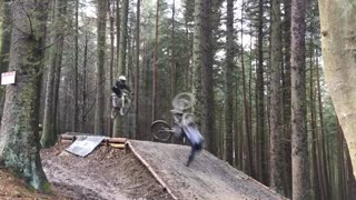 Bicycle guy jumps ramp in woods and lands short and faceplants - Video