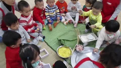 Vietnamese traditional game - Instructing children how to make Chung cake.