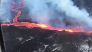 Plane flies over Iceland volcano spewing lava - Video