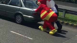 Mascot helps push broken vehicle - Video