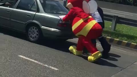 Mascot helps push broken vehicle