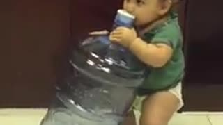Thirsty baby tries to drink from 5 gallon water jug - Video