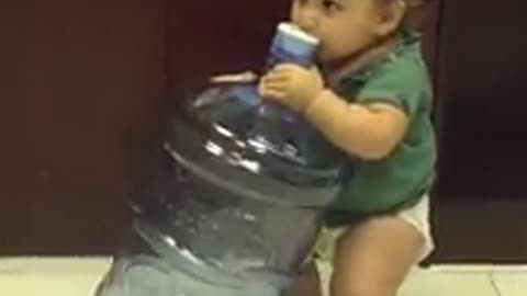 Thirsty baby tries to drink from 5 gallon water jug