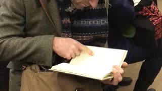 Old guy black beanie reading book pointing at words