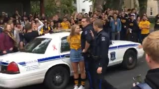 Teen girl in yellow shirt is being arrested by police, crowd chants