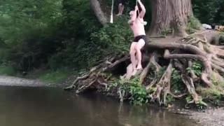 Shirtless man rope swing lands in shallow water