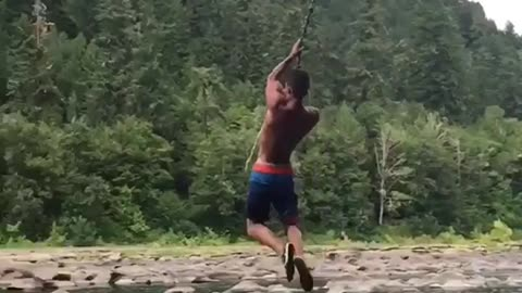 Rope swing fail guy spins flips and lands on back water lake