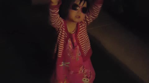 girl wearing sunglasses singing twinkle little star at night