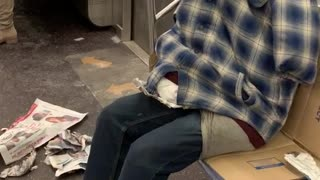 Clothes stuffed with pillows, looks like person sitting on subway, no head