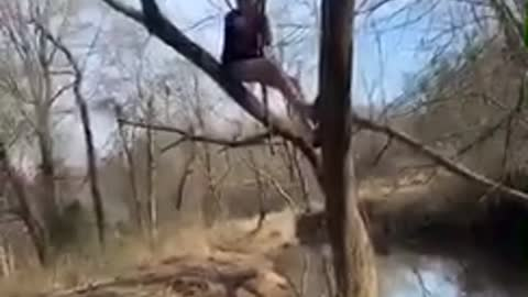 Guy tries to swing on vine over a river, vine breaks and guy falls into water