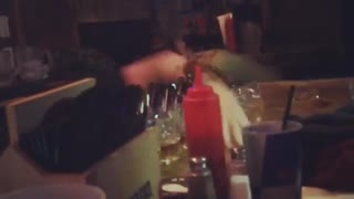 Guy in black shirt falling off table and spilling drinks