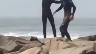 Surfer doing stretches on a rocky shore