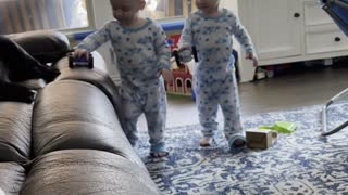 Twin toddlers amused by rolling toy cars on the sofa