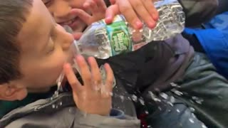 Boy feeds little brother water, squeezes water bottle and splashes his face