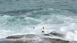 Guy tries to jump into water off rocks at beach but gets pushed back by waves every time - Video