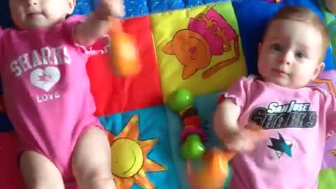 Twin babies shake mariachi rattles in unison