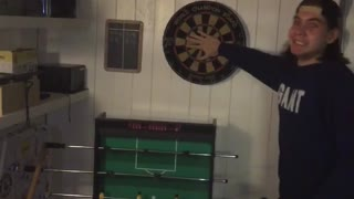 Guy shoots dart in between guy in blue shirts fingers and makes it - Video