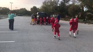 Youth Football Team Pushes Truck Around Parking Lot