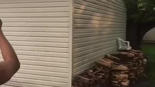 Shirtless man jumps from garage onto white table in back yard - Video