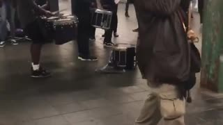 Old man with cane dances to drummers in subway