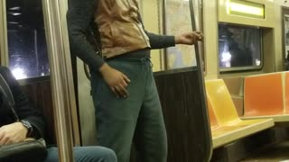 Man plays the air guitar by himself on subway train