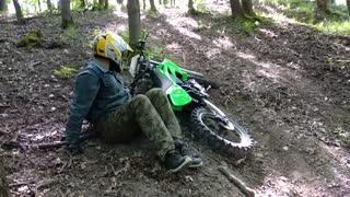 Green dirtbike tries to go up dirt hill guy falls over - Video