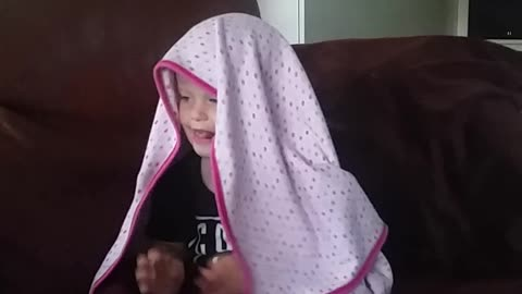 Funny baby can't get blanket straight whilst watching Trolls