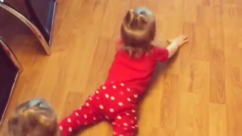 Twin baby girls mop the floors by crawling backwards