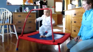 Adorable baby loves jumping on trampoline