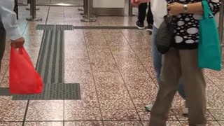 Boy in red yells at phone in subway station