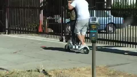 Two guys riding scooter together caps