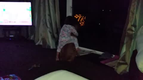 Cute baby rides boxer dog like a horse