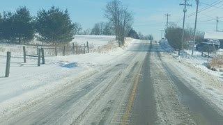 Driving down snowy county road